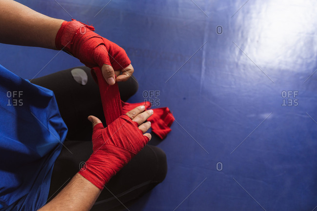 Overhead view low section of a young mixed race male boxer in a boxing ring wrapping his hands