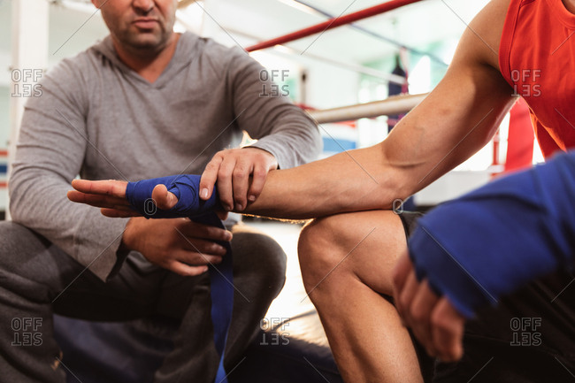 Front view mid section of a young Caucasian male boxer in a boxing ring having his hands wrapped by a middle aged Caucasian male trainer