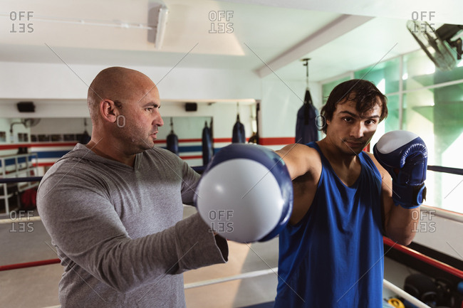 Front view close up of a young mixed race male boxer punching being instructed by a middle aged Caucasian male trainer in a boxing gym