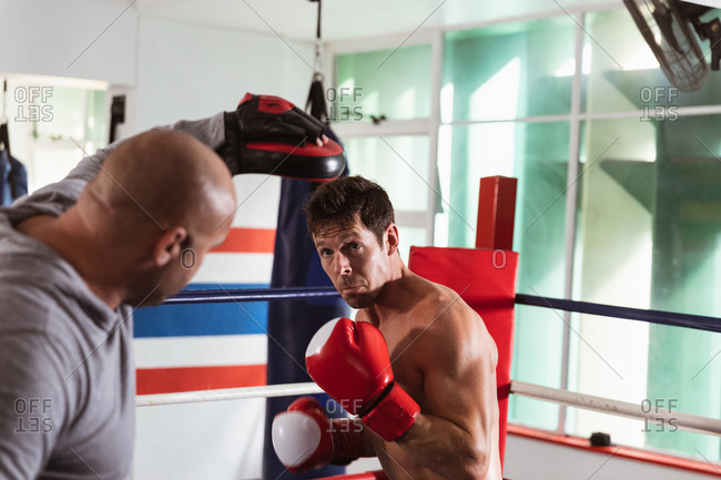 Front view close up of a young Caucasian male boxer in a boxing ring listening to a middle aged Caucasian male trainer