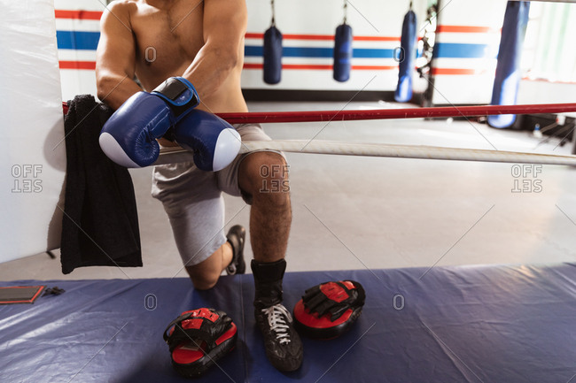 Front view low section of a young mixed race male boxer by a boxing ring leaning on a rope