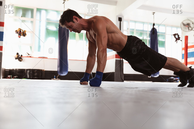 Side view of a young Caucasian male boxer doing push ups in a boxing gym