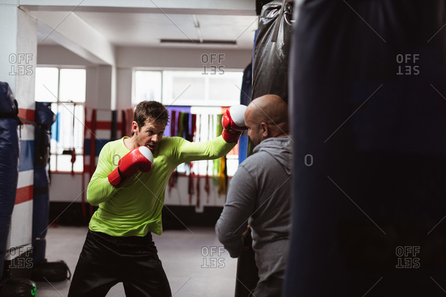 Front view of a young Caucasian male boxer punching a punchbag held by a middle aged Caucasian male trainer in a boxing gym