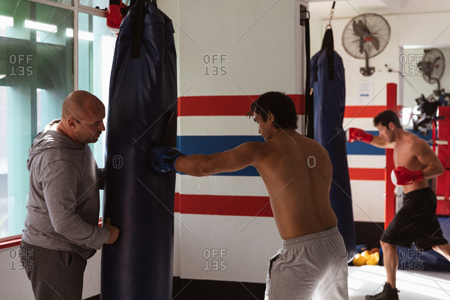 Side view of a young mixed race male boxer punching a punchbag held by a middle aged Caucasian male trainer with a young Caucasian male boxer training in the background