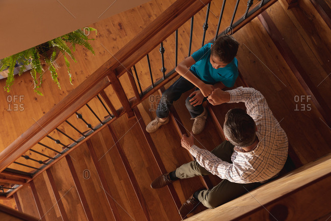 Overhead view of a middle aged Caucasian man celebrating with a fist bump with his pre teen son sitting on a staircase