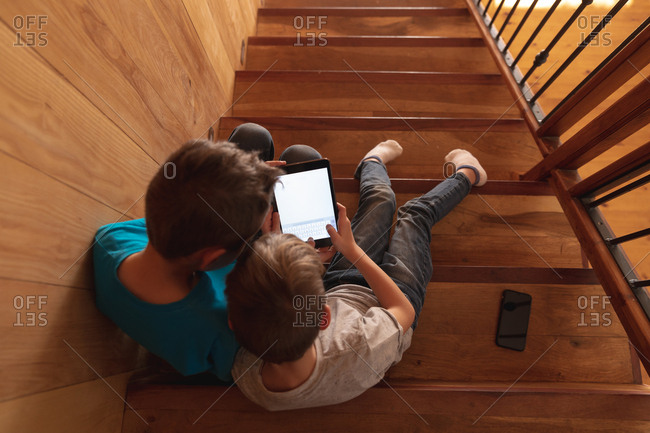 Overhead view of two pre teen Caucasian boys sitting on a staircase at home, using a tablet computer and a smartphone