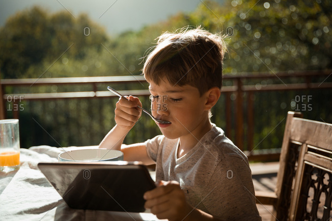 Front view close up of a pre teen Caucasian boy sitting at a table in a garden, using a tablet computer