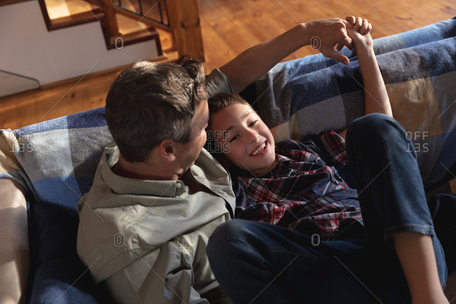 Side view of a middle aged Caucasian man sitting with his pre teen son on a couch and talking