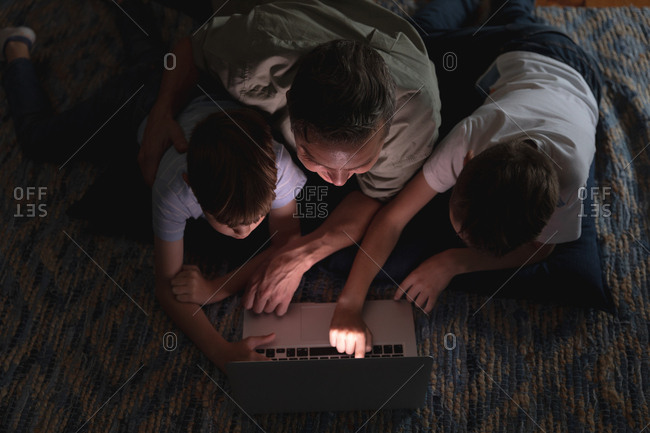 Overhead view of a middle aged Caucasian man and his pre teen sons using a laptop computer in a sitting room