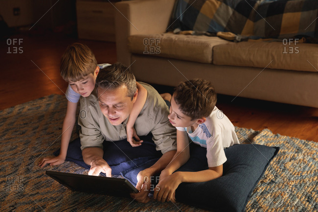 Front view of a middle aged Caucasian man and his pre teen sons using a laptop computer in a sitting room