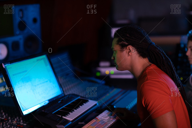 Side view close up of a young Caucasian male sound engineer sitting and working at a mixing desk in a recording studio using a computer