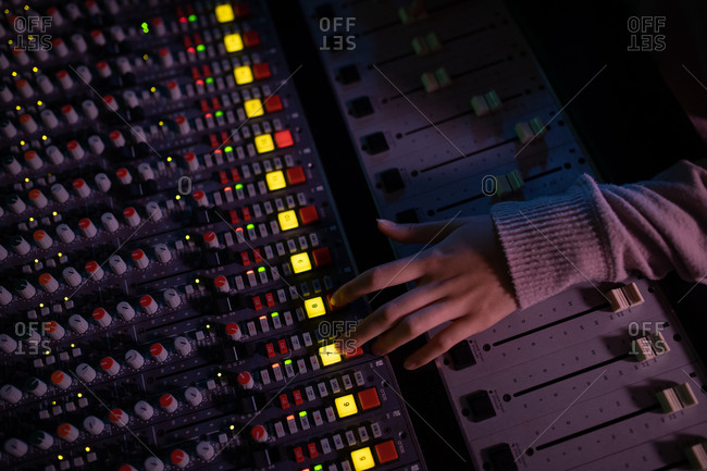 Overhead view of the hand of a young Caucasian female sound engineer operating a mixing desk in a recording studio