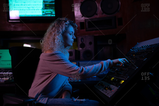 Side view close up of a young Caucasian female sound engineer sitting and working at a mixing desk in a recording studio