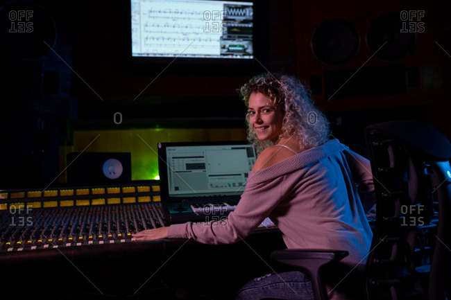 Rear view of a young Caucasian female sound engineer sitting and working at a mixing desk in a recording studio turning and smiling to camera