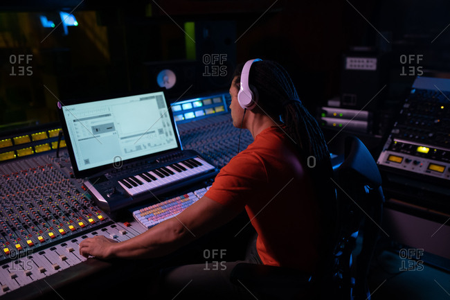 Side view of a young mixed race male sound engineer sitting and working at a mixing desk in a recording studio using a computer and wearing headphones