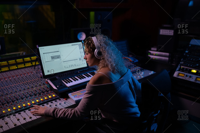 Side view close up of a young Caucasian female sound engineer sitting and working at a mixing desk in a recording studio wearing headphones