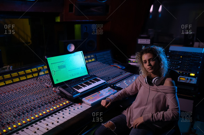 Portrait of a young Caucasian female sound engineer sitting at a mixing desk in a recording studio looking to camera