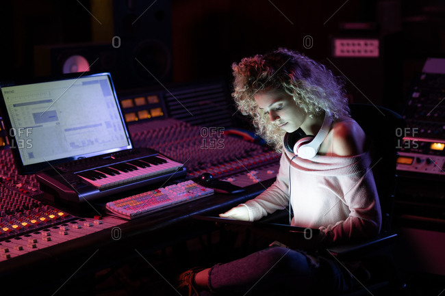 Side view close up of a young Caucasian female sound engineer sitting and working at a mixing desk using a laptop computer in a recording studio
