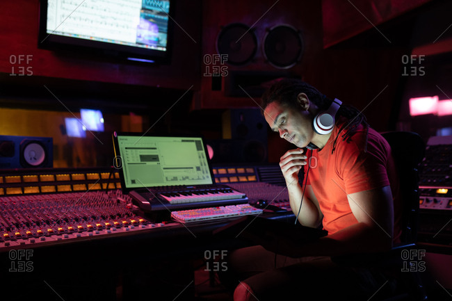 Side view close up of a young mixed race male sound engineer sitting and working at a mixing desk using a laptop computer in a recording studio