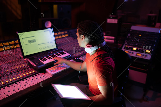 Side view close up of a young mixed race male sound engineer sitting and working at a mixing desk in a recording studio using a computer and a midi controller keyboard