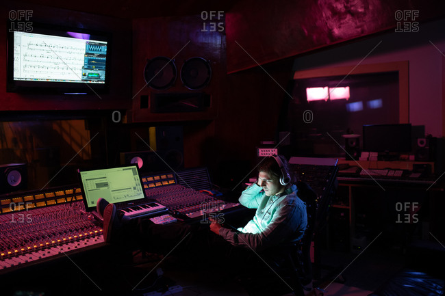 Side view of a young Caucasian male sound engineer sitting and working at a mixing desk in a recording studio using a laptop computer and wearing headphones