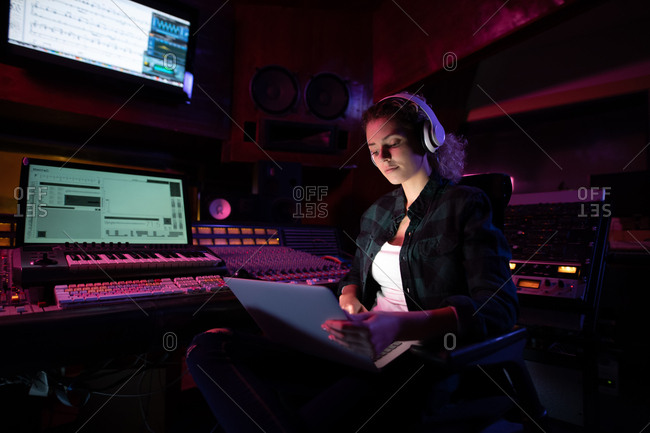 Front view of a young Caucasian female sound engineer sitting and working at a mixing desk in a recording studio using a laptop computer and wearing headphones