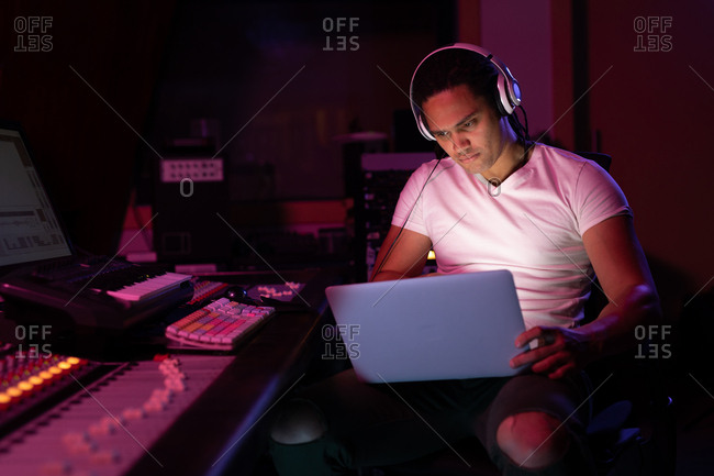 Front view close up of a young mixed race male sound engineer sitting and working at a mixing desk in a recording studio using a laptop and wearing headphones