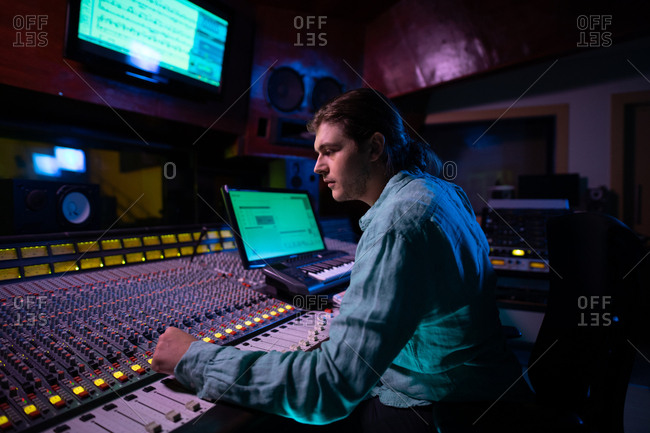 Side view close up of a young Caucasian male sound engineer sitting and working at a mixing desk in a recording studio