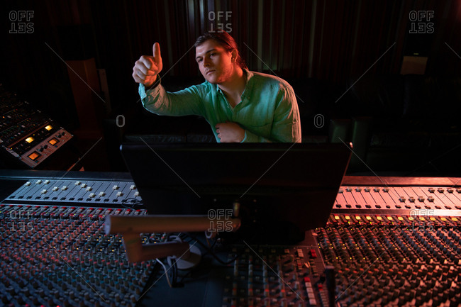 Front view of a young Caucasian male sound engineer sitting and working at a mixing desk in a recording studio giving a thumbs up sign during a recording session