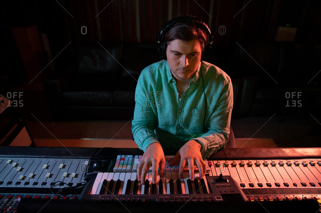 Front view close up of a young Caucasian male sound engineer sitting at a mixing desk in a recording studio using a midi keyboard