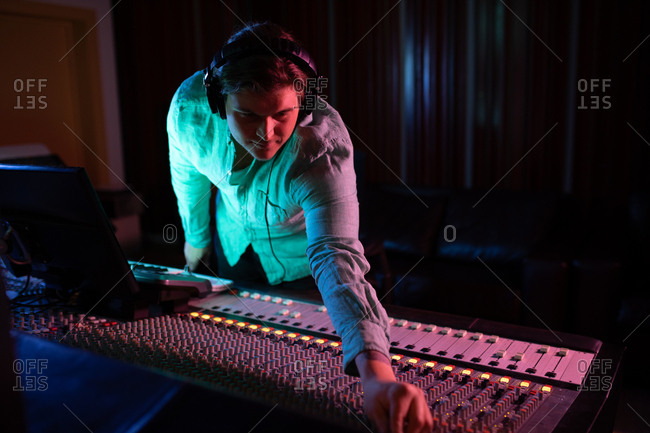 Front view close up of a young Caucasian male sound engineer wearing headphones reaching across a mixing desk in a recording studio to adjust a channel setting