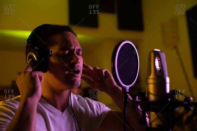 Side view close up of a young mixed race male singer wearing headphones and singing in front of a microphone in a recording studio, with his eyes closed