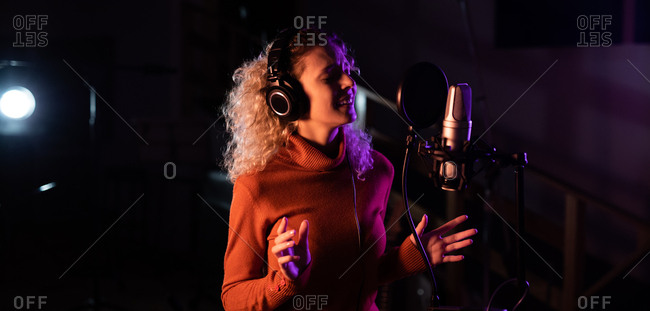 Side view of a young Caucasian female singer wearing headphones and singing in front of a microphone in a recording studio, gesturing and with her eyes closed
