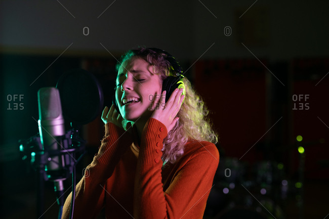 Side view close up of a young Caucasian female singer wearing headphones and singing in front of a microphone in a recording studio, with her eyes closed