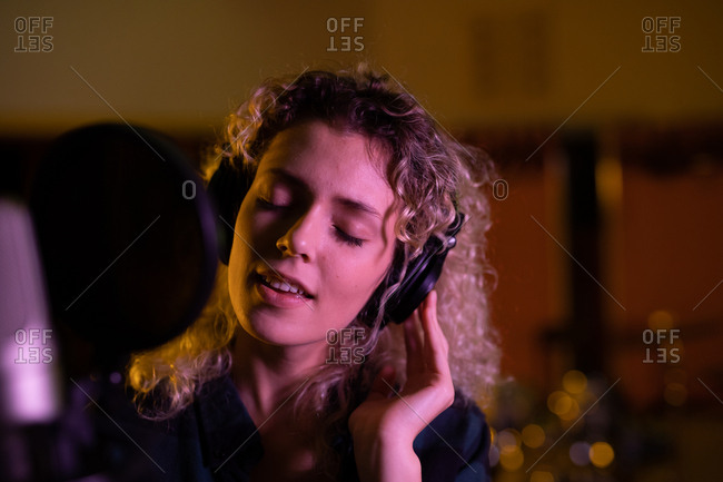 Front view close up of a young Caucasian female singer wearing headphones standing in front of a microphone in a recording studio, with her eyes closed