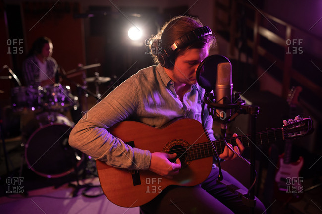Front view close up of a young Caucasian man wearing headphones sitting and playing an acoustic guitar in front of a microphone during a session at a recording studio with a drummer in the background