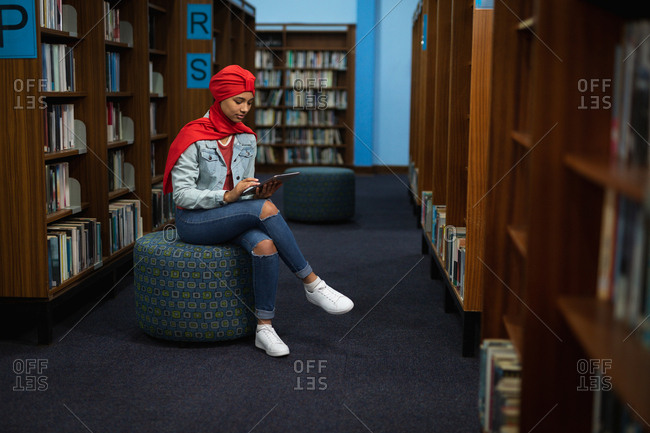 Side view of a young Asian female student wearing a turban using a tablet computer and studying in a library