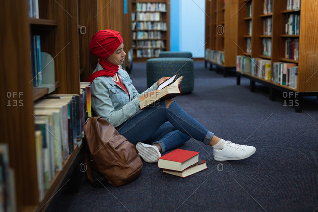 Side view close up of a young Asian female student wearing a turban reading a book and studying in a library