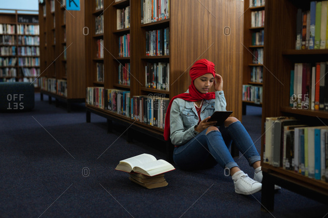 Front view close up of a young Asian female student wearing a turban using a tablet computer and studying in a library