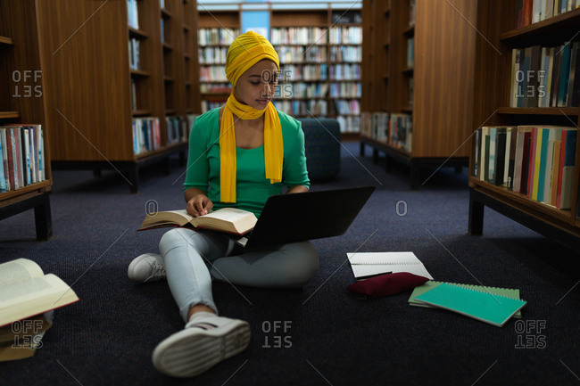 Front view close up of a young Asian female student wearing a hijab holding a book, using a laptop computer and studying in a library