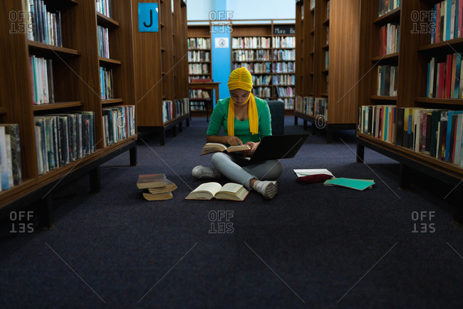 Front view of a young Asian female student wearing a hijab holding a book, using a laptop computer and studying in a library