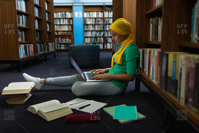 Side view close up of a young Asian female student wearing a hijab using a laptop computer and studying in a library