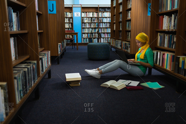 Side view of a young Asian female student wearing a hijab using a laptop computer and studying in a library