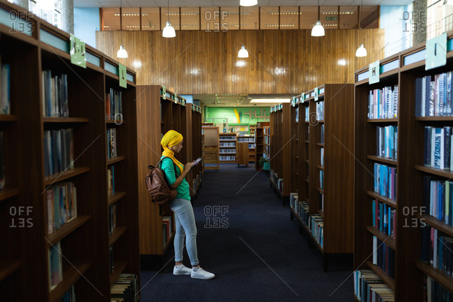 Side view of a young Asian female student wearing a hijab using a smartphone in a library
