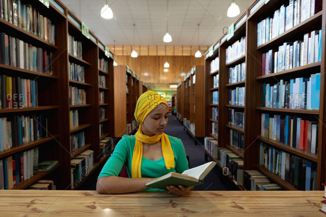 Front view close up of a young Asian female student wearing a hijab reading a book and studying in a library