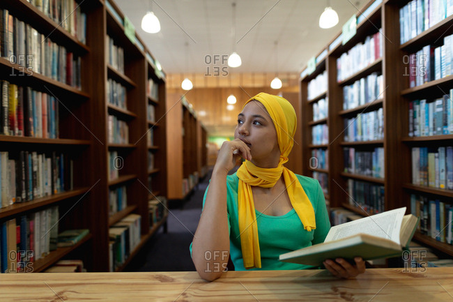 Front view close up of a young Asian female student wearing a hijab holding a book and studying in a library