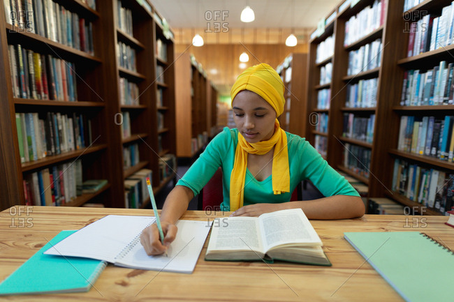 Front view close up of a young Asian female student wearing a hijab making notes and studying in a library