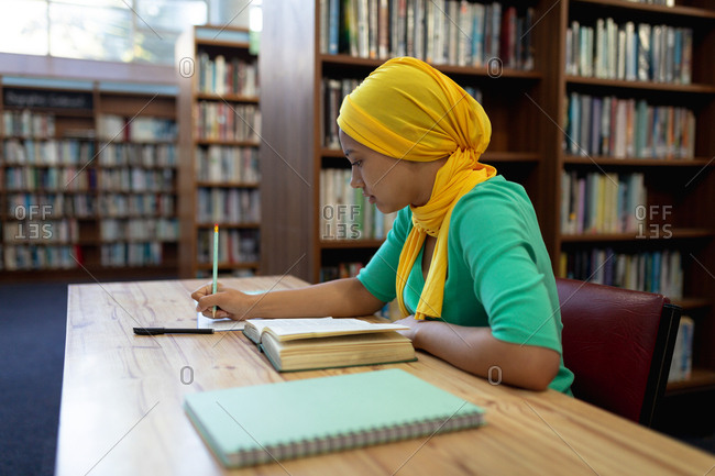 Side view close up of a young Asian female student wearing a hijab making notes and studying in a library