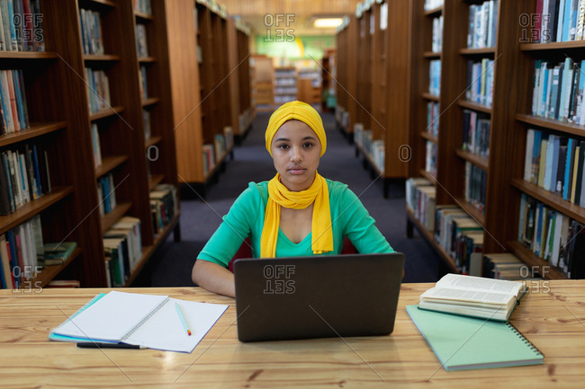 Portrait of a young Asian female student wearing a hijab using a laptop computer and studying in a library