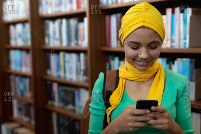 Front view close up of a young Asian female student wearing a hijab using a smartphone in a library